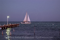 Sailboat sails past pier